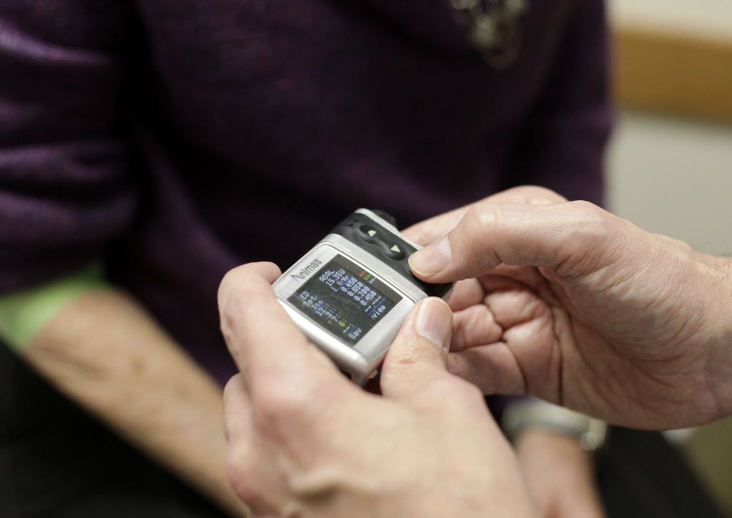 Endocrinologist Dr. Howard Baum checks the insulin pump of patient Connie Hedgecoke of Garland during her quarterly diabetes checkup in his office at Medical City in Dallas.