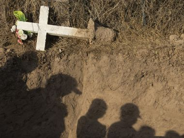 Anthropology students from Texas State University look down into the grave site of unidentified, deceased migrants at a cemetery in La Grulla, Texas. The students work under Kate Spradley's leadership with Operation Identification, an applied anthropology project that helps catalog and identify human remains of migrants who have perished in South Texas.