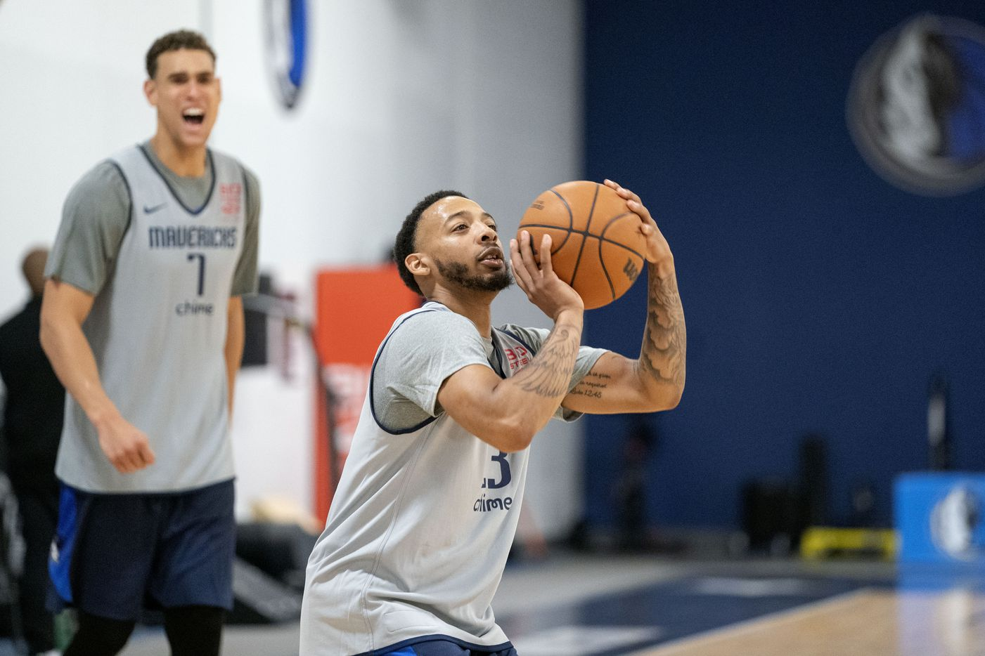 Dallas Mavericks guard Carlik Jones (23) shoots a 3-pointer as center Dwight Powell (7) jokingly distracts him during the first practice of training camp, Tuesday, September 28, 2021 at the Dallas Mavericks Training Center in Dallas. (Jeffrey McWhorter/Special Contributor)