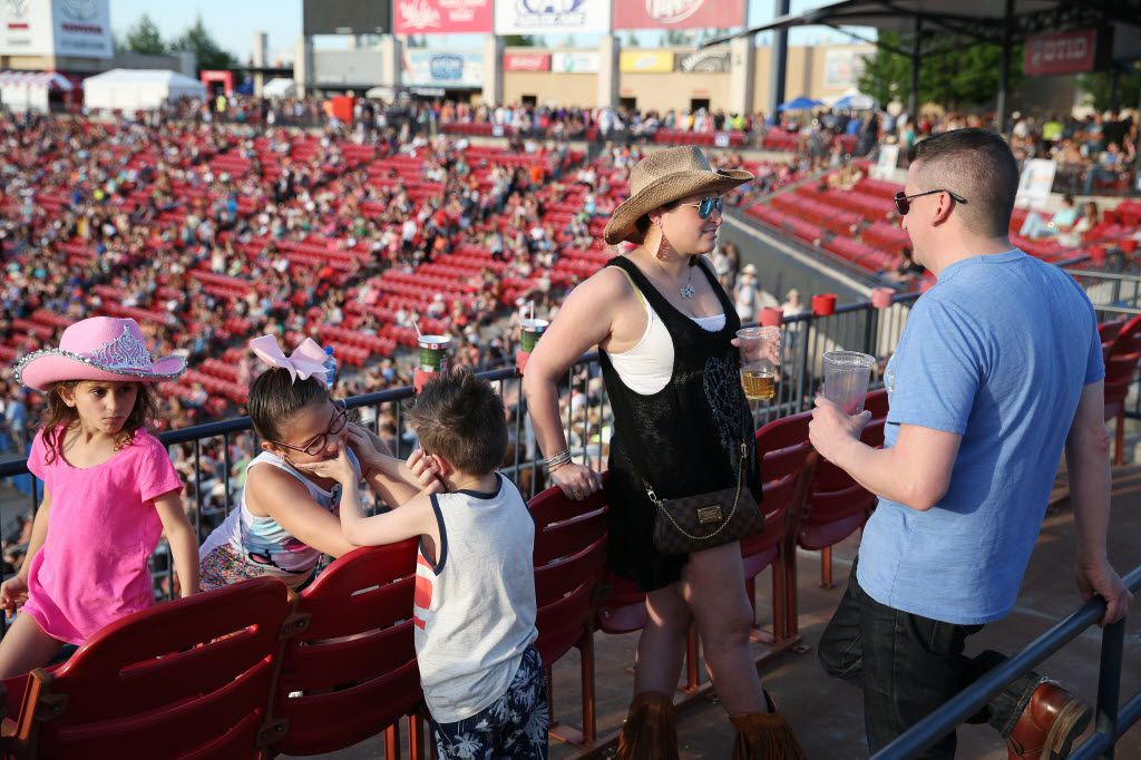 (From left) Alana Horton, 7, play with her siblings, Beanna Horton, 10, and Grant Horton, 5, as her parents, Jen Horton and Joe Horton, of Frisco, Texas, stand nearby during the Off the Rails Country Music Fest at Toyota Stadium. (Andy Jacobsohn/The Dallas Morning News)