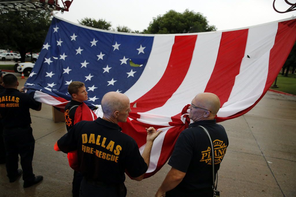 Plano fire Captain Chris Bechtold (right) and Dallas fire Captain Mike Bueller (second from right) prepare to fly a large U.S. flag above the main entrance to Prestonwood Baptist Church in Plano, Texas for the service and memorial of Dallas police officer Michael Krol, Friday, July 15, 2016.