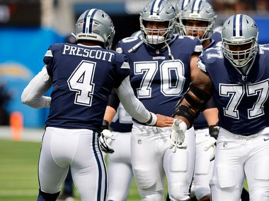 Dallas Cowboys quarterback Dak Prescott (4) greets his guard Zack Martin (70) and offensive tackle Tyron Smith (77) during pregame warmups before their game against the Los Angeles Chargers at SoFi Stadium in Inglewood, California, Sunday, September 19, 2021.