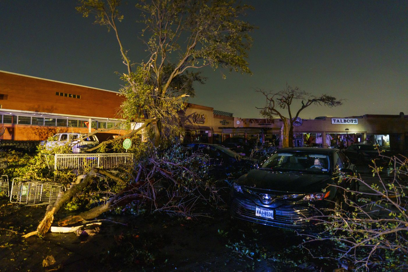 A woman sits in a car surrounded by tornado damage near the intersection of Royal and Preston on Sunday, Oct. 20, 2019, in Dallas. (Smiley N. Pool/The Dallas Morning News)