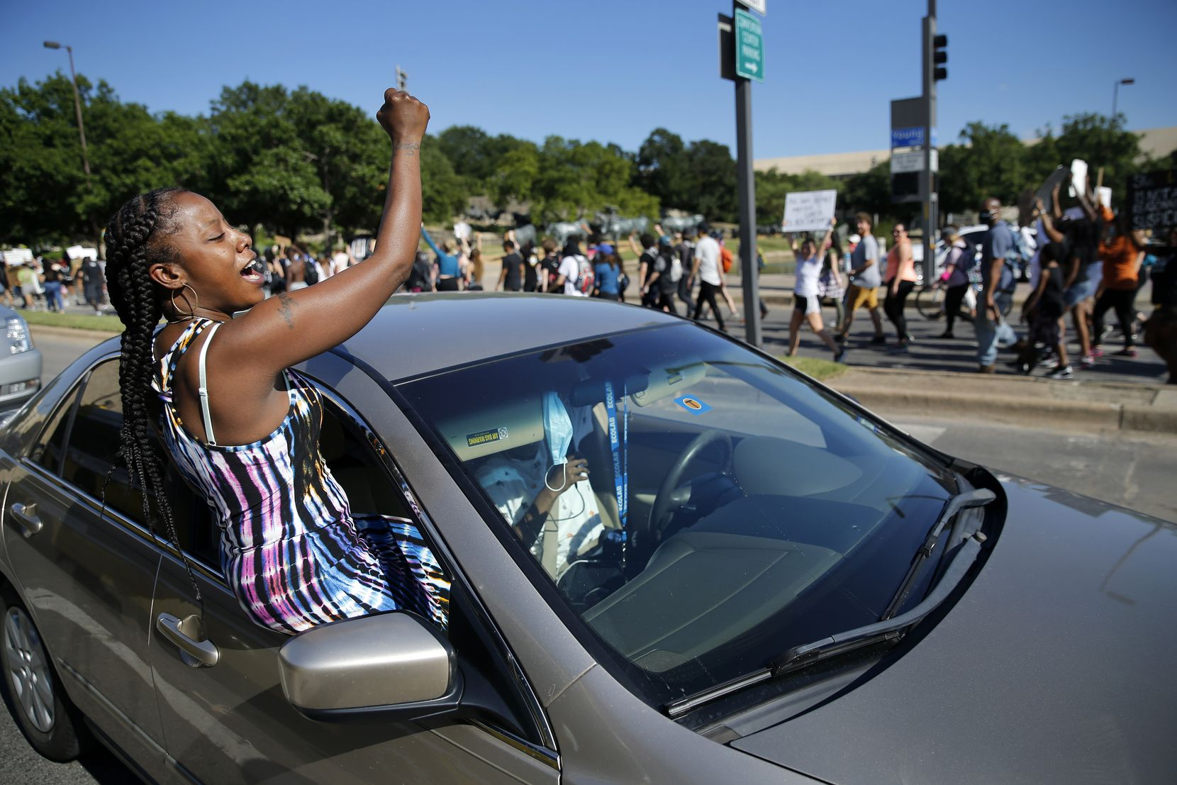 Angel Brown of Dallas crawls out of her car window to support protesters marching in Dallas on Wednesday.
