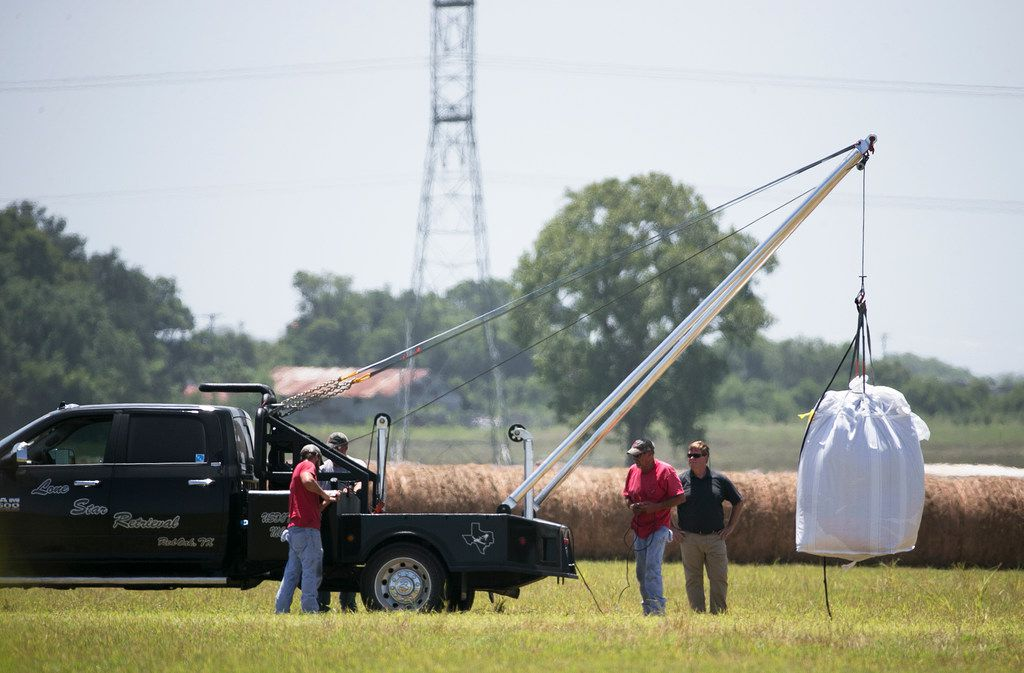 A crew hoists a bag holding the remains of a hot air balloon that crashed in 2016 onto a waiting truck at the scene near Lockhart. The U.S. House has approved a measure requiring medical checks for commercial hot air balloon pilots in an effort to avoid another crash like the one near Lockhart that killed 16 people.