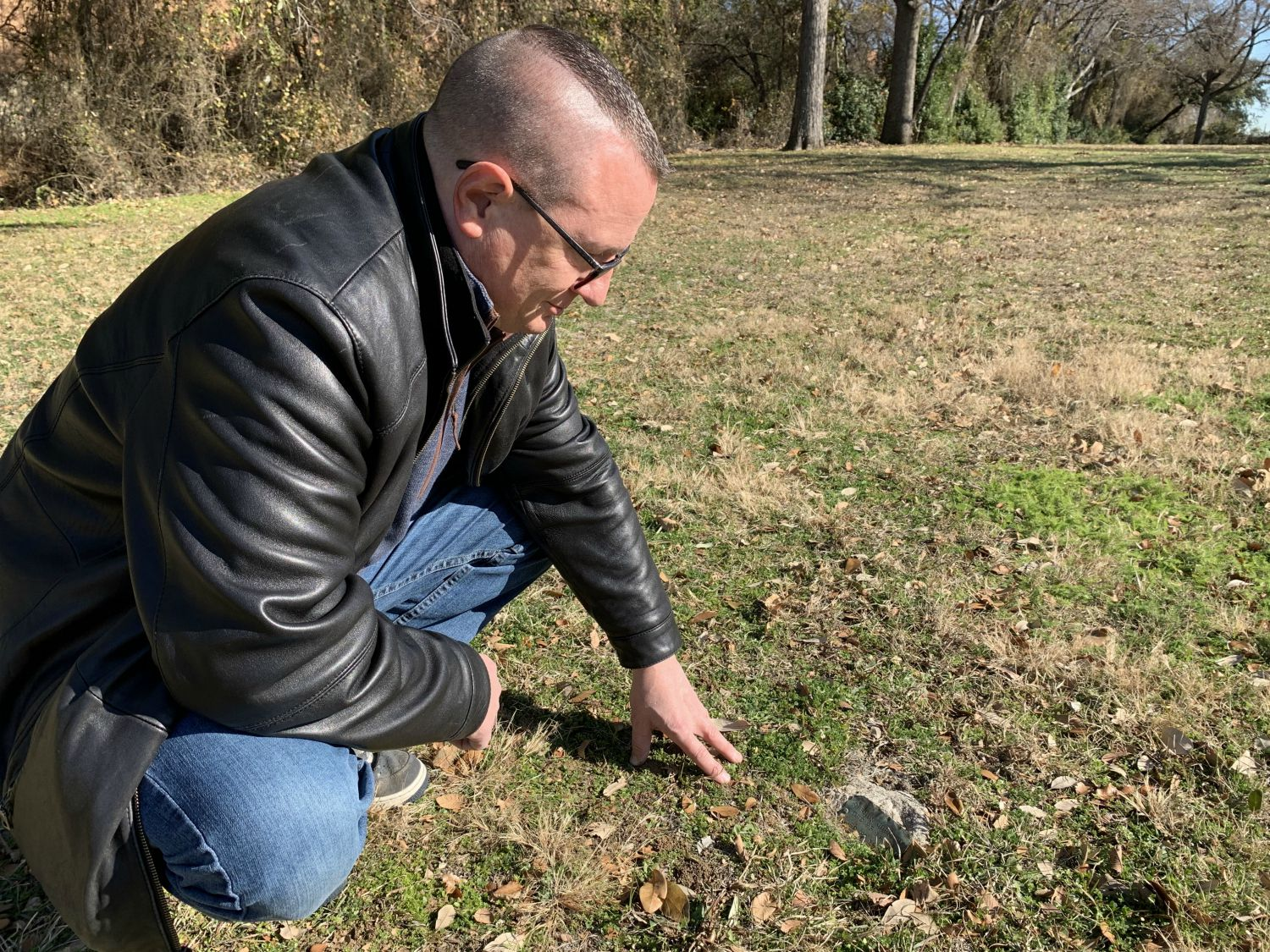 Dan Babb inspects one of the surviving markers at the old Dallas City Cemetery, which has become his obsession — or addiction, depending on whom you ask.