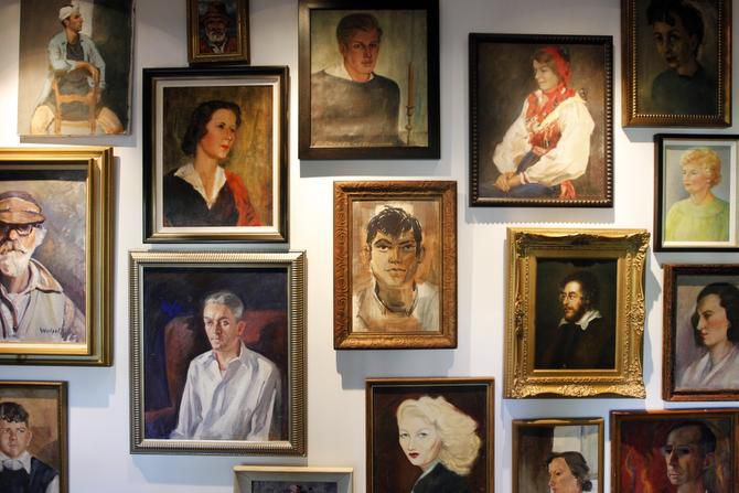 A collection of painted portraits, displayed gallery style, lines both sides of the hallway.