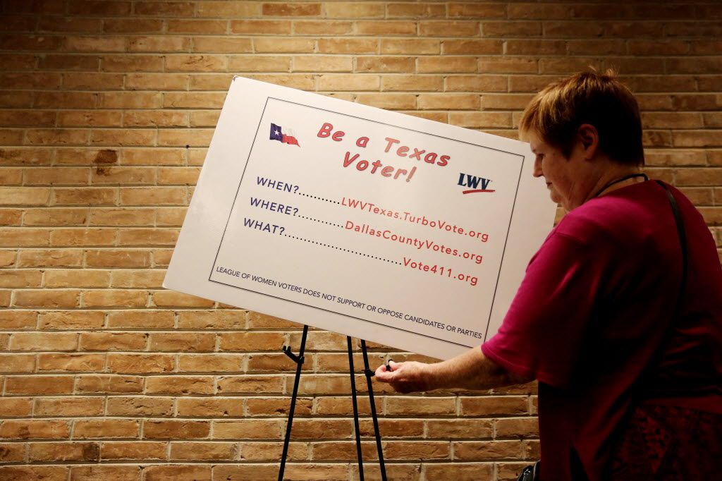 Elizabeth Walley, of Mesquite, Texas, part of the League of Women Voters, hangs a poster before a deputy voters registrar class.