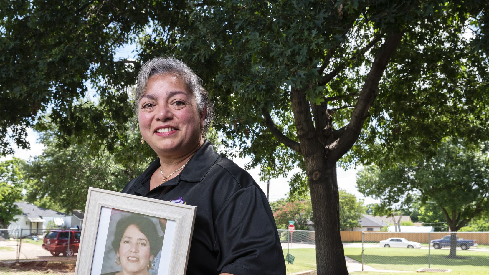 Diana C. Vargas-Martínez, 48, an instructional coach at Leila P. Cowart Elementary, with a portrait of her mother Marisela Vargas near a tree she planted with her mom back in 1992, outside the school in Dallas, on Thursday, July 01, 2021.
