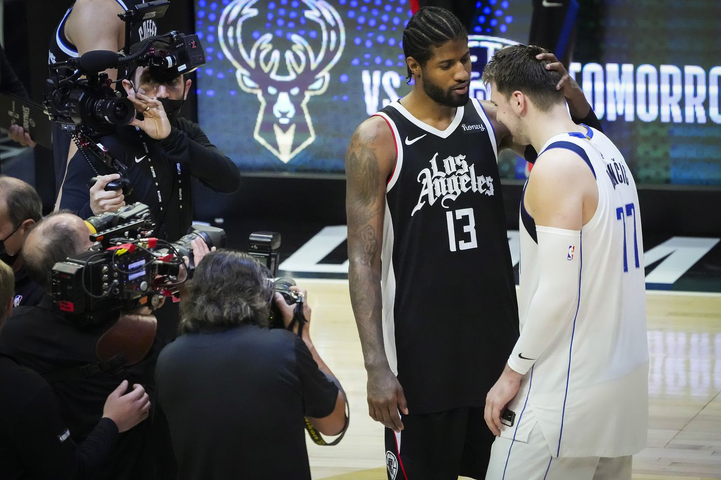 Dallas Mavericks guard Luka Doncic (77) ins consoled by LA Clippers guard Paul George (13) after the Clippers victory in Game 7 of an NBA playoff series at the Staples Center on Sunday, June 6, 2021, in Los Angeles.