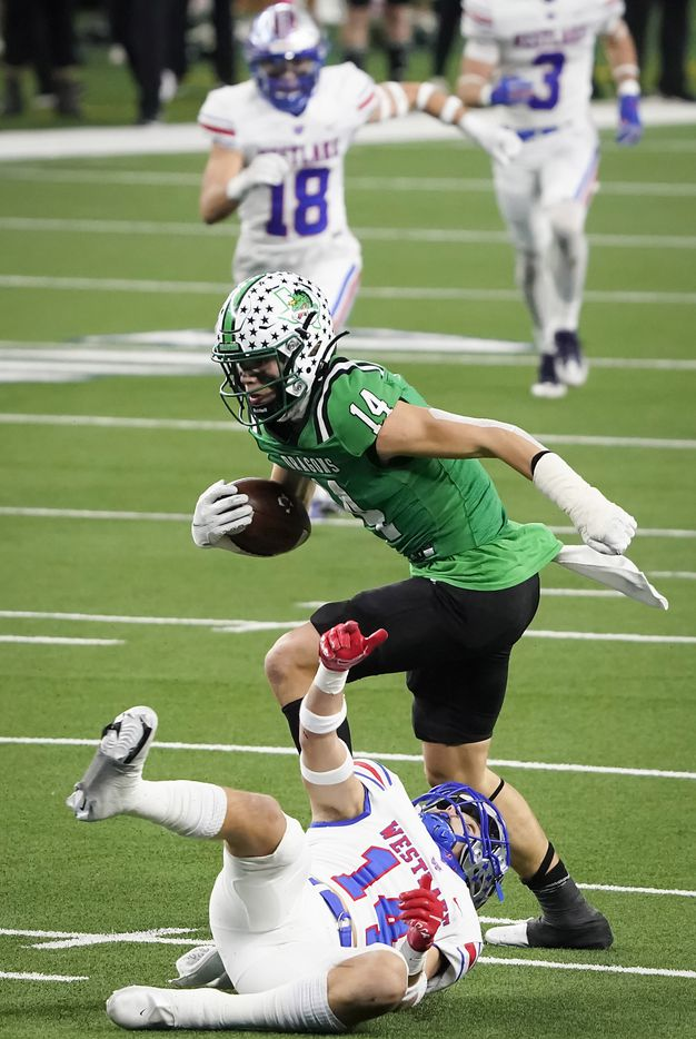 Southlake Carroll wide receiver Brady Boyd (14) break the tackles of Austin Westlake defensive back Michael Taaffe (14) on a 49-yard touchdown play during the first quarter of the Class 6A Division I state football championship game at AT&T Stadium on Saturday, Jan. 16, 2021, in Arlington, Texas.