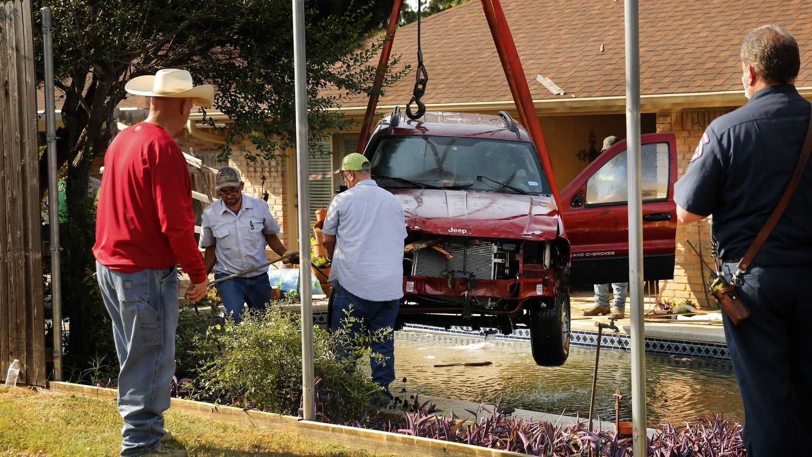 A wrecker crew uses a crane to lift a Jeep Grand Cherokee from a backyard pool on Clemson Drive in Arlington on Monday. The driver, who crashed through the fence on W. Beady Road, suffered minor injuries.