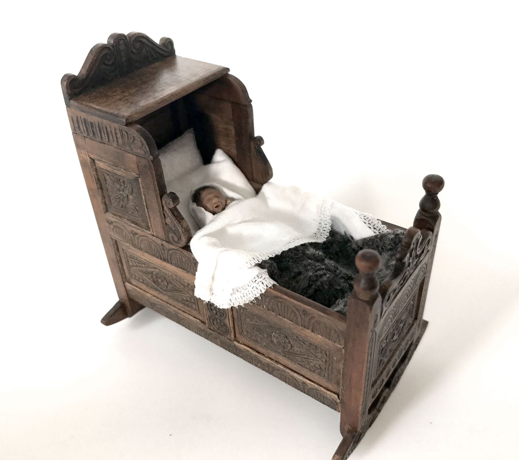 A cradle made by Ann High, with linens and baby made by Kevin Mulvany and Susie Rogers, who consulted on the creation of miniatures for a three-part miniseries that aired on PBS Masterpiece, based on Jessie Burton's 2014 best-selling book, The Miniaturist.