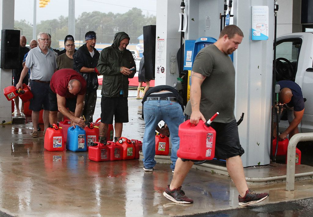 People wait in line to fill gas cans at a gas station that was damaged when Hurricane Florence hit the area on Sept. 15, 2018 in Wilmington, N.C..