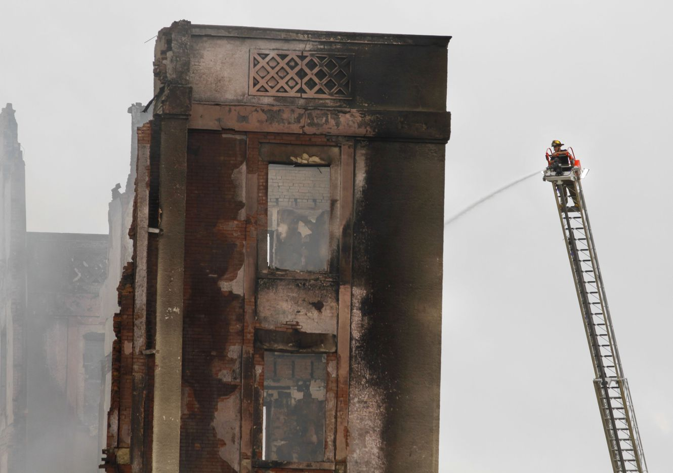 A Dallas Fire-Rescue team member sprays water from atop a ladder on the Ambassador Hotel after the overnight fire.