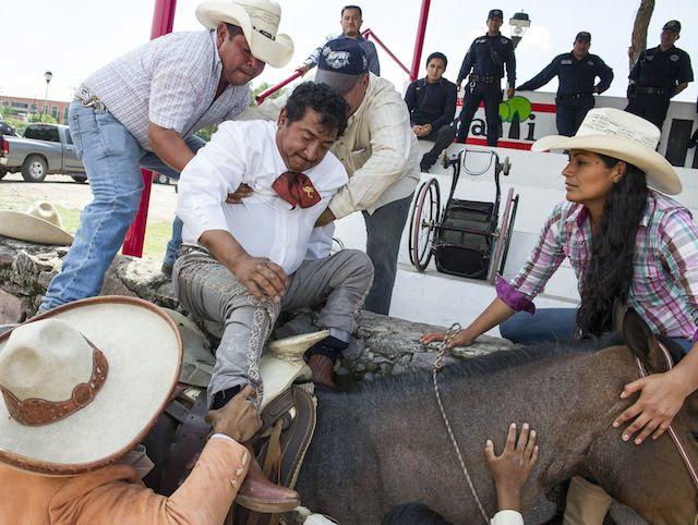 Salvador Espinoza recibe ayuda para montar su caballo en Cuautitlán Izcalli, en el Estado de México.