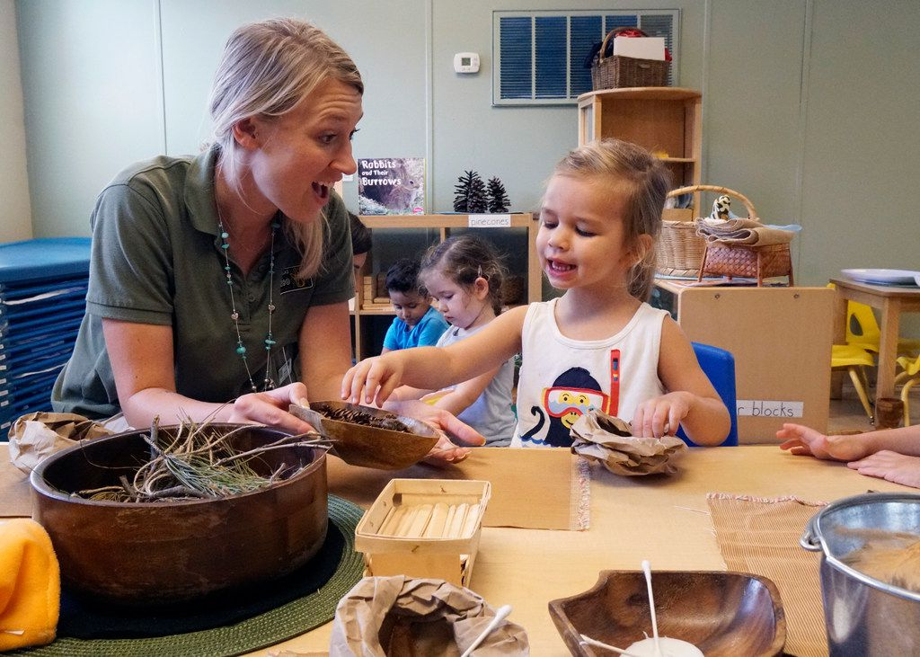 Sierra Bair and Virginia Davis, 4 make a bird nest at the Dallas Zoo's Wild Earth Preschool in August, 2018. The school uses nature to teach the same lessons children learn in traditional preschool.