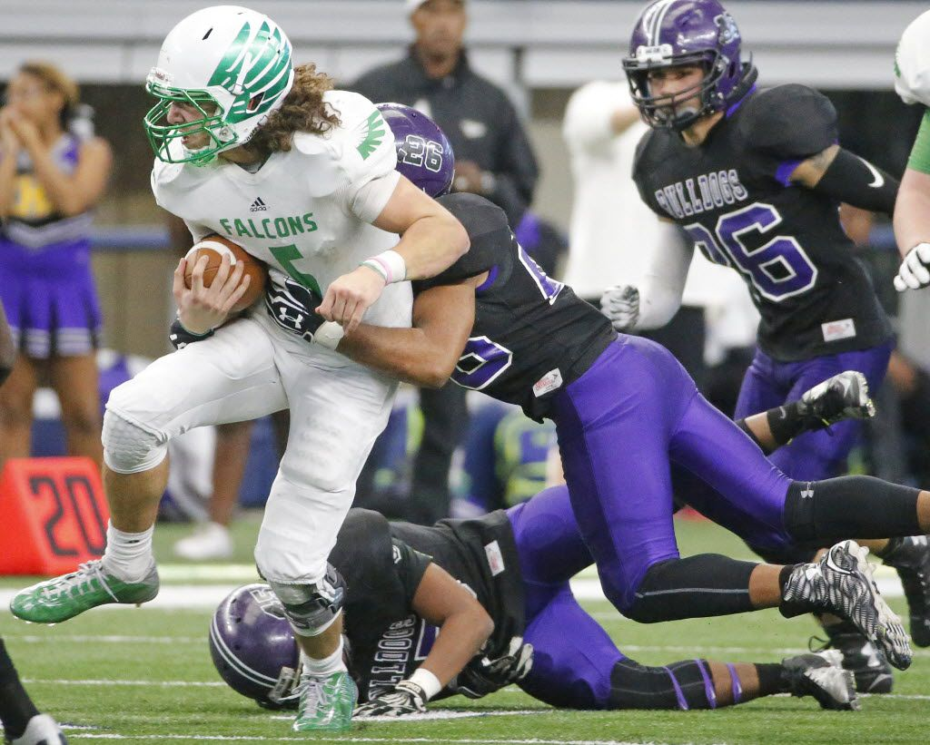 Lake Dallas quarterback Dagan Haehn (5) runs for yardage as Everman's Jaylon Sparks (26) tries to make the tackle during the Lake Dallas High School Falcons vs. the Everman High School Bulldogs playoff football game at AT&T Stadium in Arlington on Saturday, December 5, 2015. (Louis DeLuca/The Dallas Morning News)