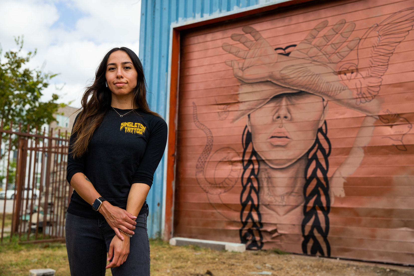 Artist Rose Rodriguez poses in front of the mural she's working on as part of The Wild West Mural Fest in Dallas on Thursday, Oct. 22, 2020. Rodriguez, a tattoo artist, was inspired by the Wichita people and their use of tattoos..