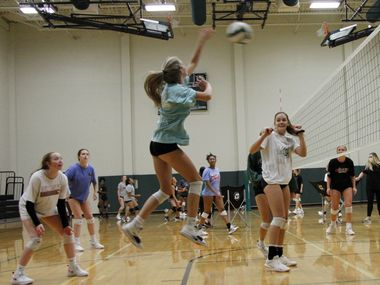 Grayson Reed skies to fire a shot as she is flanked by teammates Tatum Pavey, left, and Bryley Steinhilber, right, during a practice session for the Kennedale Lady Kats volleyball team. Under the direction of head coach Kelly Carl, the team conducted their first practice of the season at Kennedale High School in Kennedale on August 03, 2020.