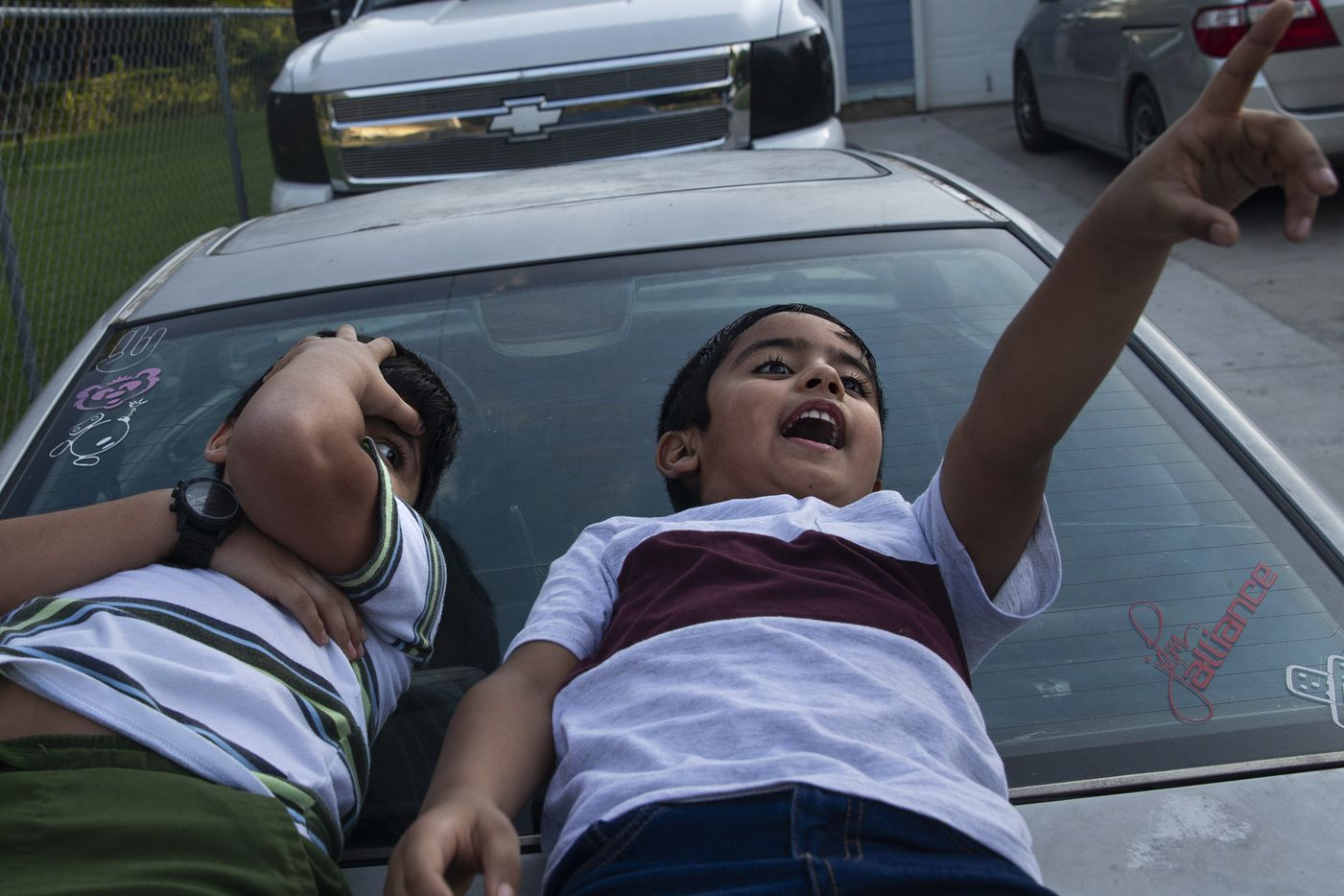 From left, brothers Jose Lara, 5, and Elias Lara, 7, gaze up at cloud shapes outside of their home in the Joppa neighborhood in South Dallas on Sunday, Aug. 2, 2020. The boys' family moved into their home, acquired through Habitat for Humanity, in 2016. Their mother Gabriela Medina said Joppa has been a great place to raise her children, and that the children are proud to tell their friends at school about the history of where they live.