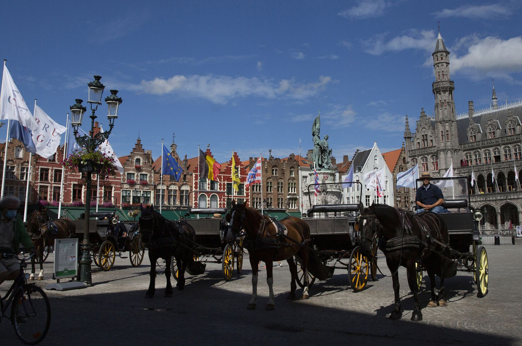 Horse and carriage tour operators wait in the center of Bruges, Belgium, as summer tourism season draws to a close.