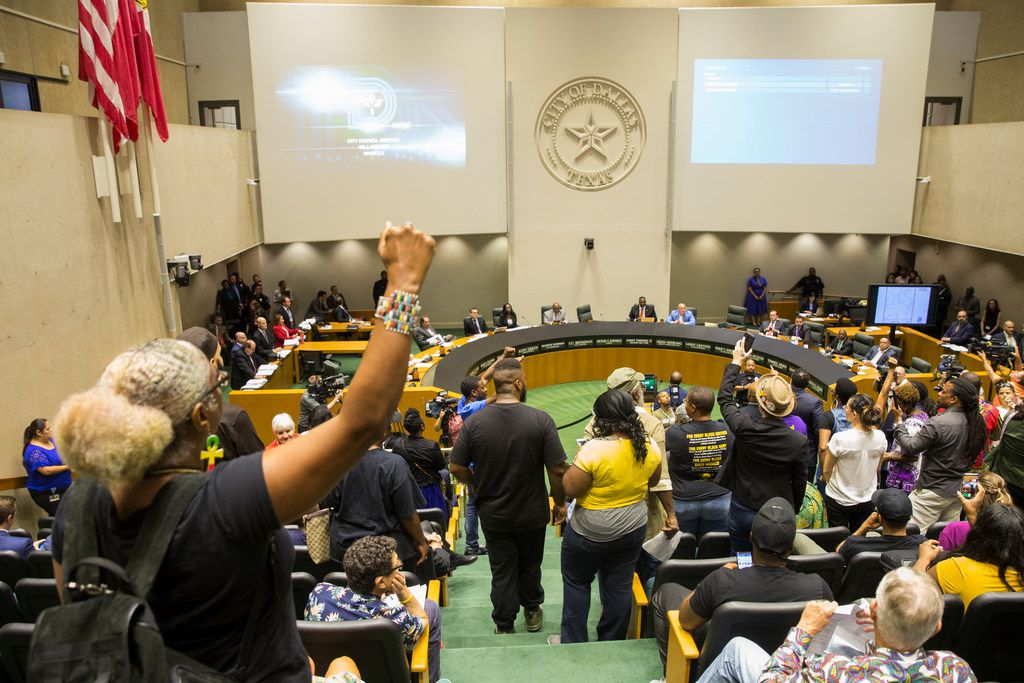 Protesters raised their fists during a Dallas City Council meeting Wednesday in which many of them asked for justice for Botham Jean.