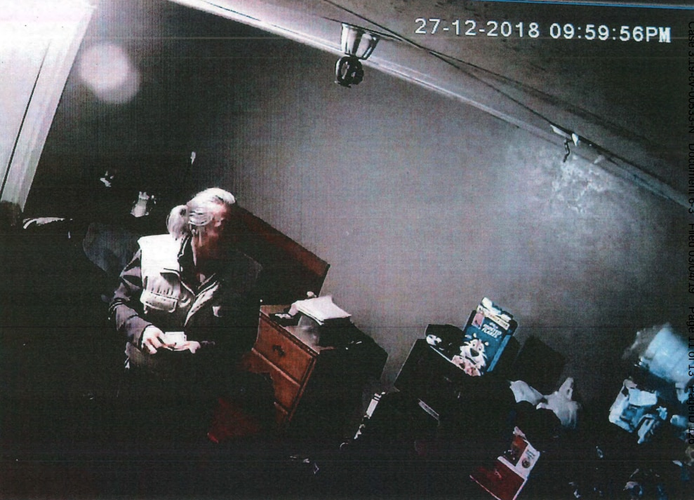"""Federal prosecutors say this is Amos Mun collecting cash in one of the """"trap"""" rooms in his Han Gil Hotel Town. It's one of many photos taken from videos entered into evidence."""
