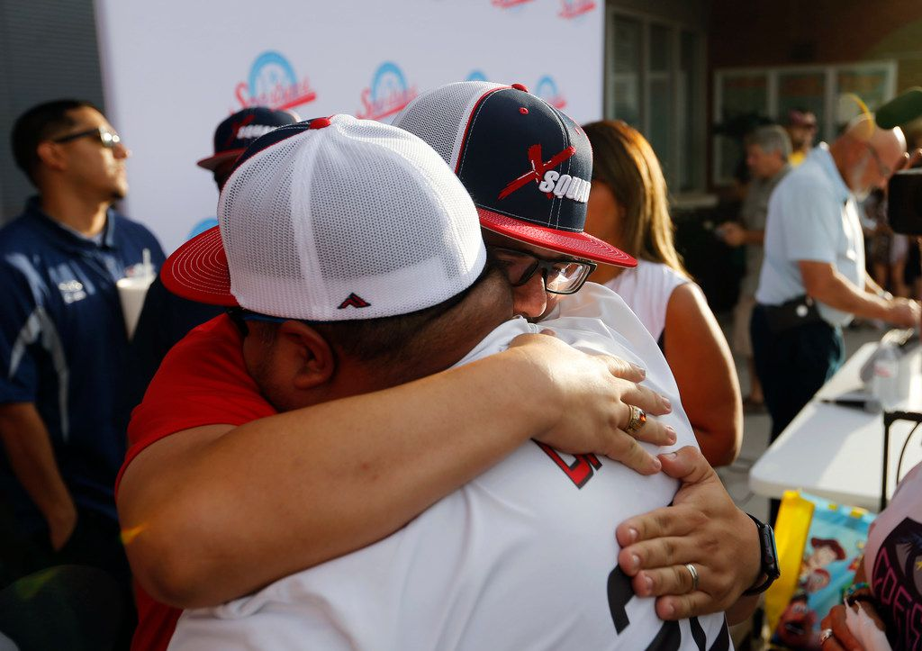 Jimmy Villatoro of El Paso (left) hugged Danny Latin (right) at a candlelight vigil at The Sportspark in El Paso on Sunday, Aug. 4, 2019. Latin's wife was injured at the Walmart shooting Saturday.
