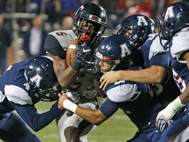 A host of Allen defenders combine to stop Trinity running back Greg Garner (5) in the third quarter during the the Trinity High School Trojans vs. the Allen High School Eagles playoff high school football game at Eagle Stadium in Allen, Texas on Friday, November 11, 2016.