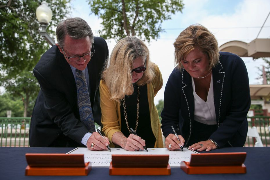 From left: DART Executive Director Gary Thomas, DART Board of Directors chairwoman Sue Bauman and acting Federal Transit Administration Administrator K. Jane Williams sign a full funding grant agreement during an announcement of expansion to the downtown Plano DART station on Thursday.