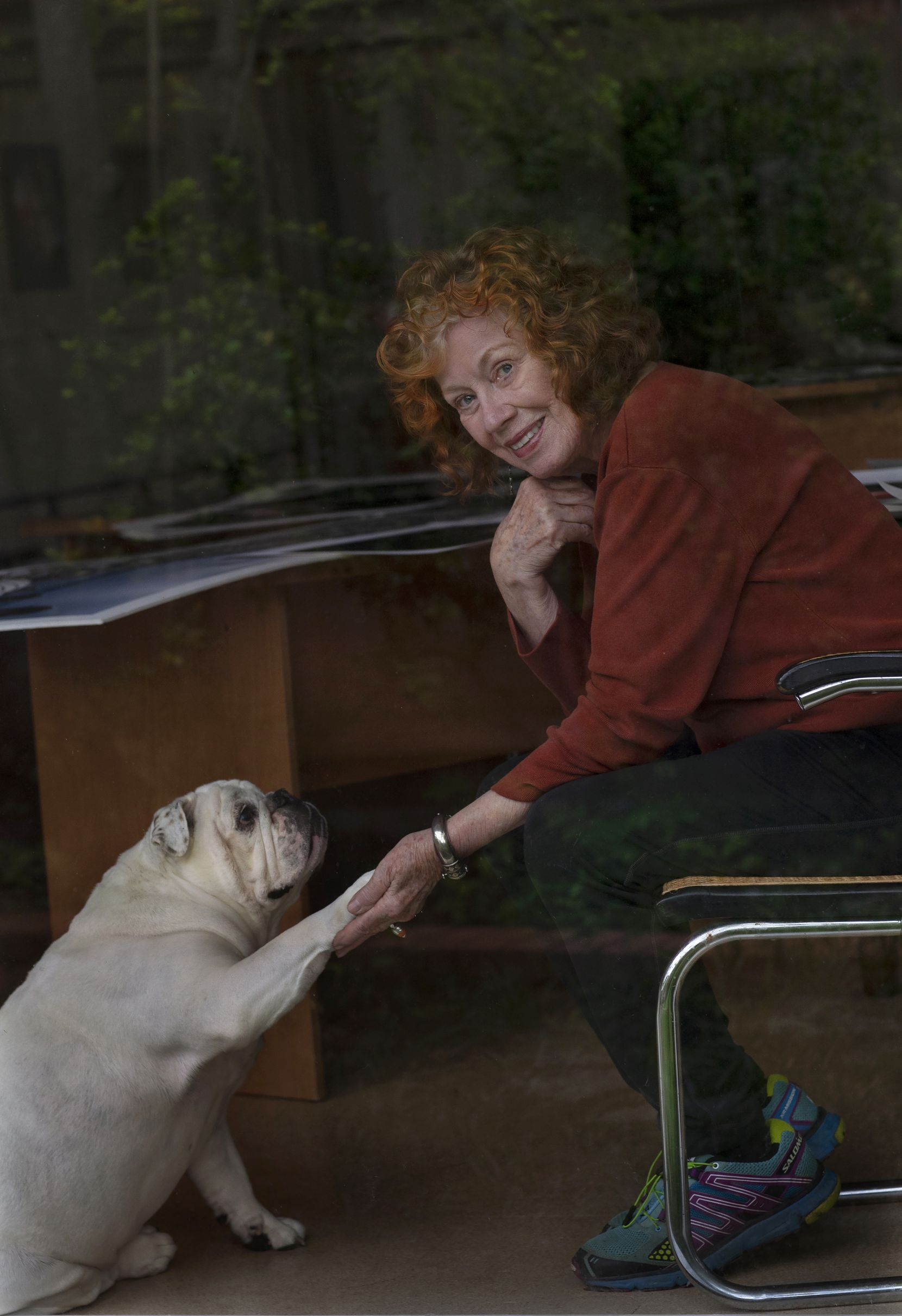 Photographer Carolyn Brown and her English bulldog Ellie Mae, photographed behind glass, are spending lots of time at Brown's home and in her garden.