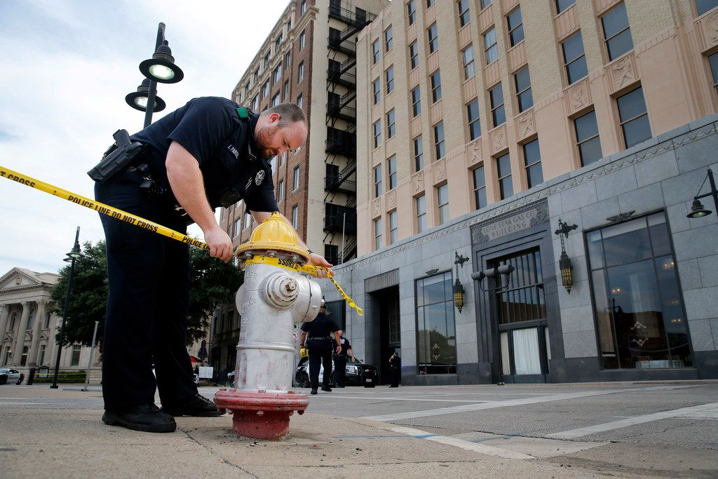 Dallas police string crime scene tape along Harwood St in downtown Dallas after shooting at the Lone Star Gas Lofts, Friday, July 26, 2019.