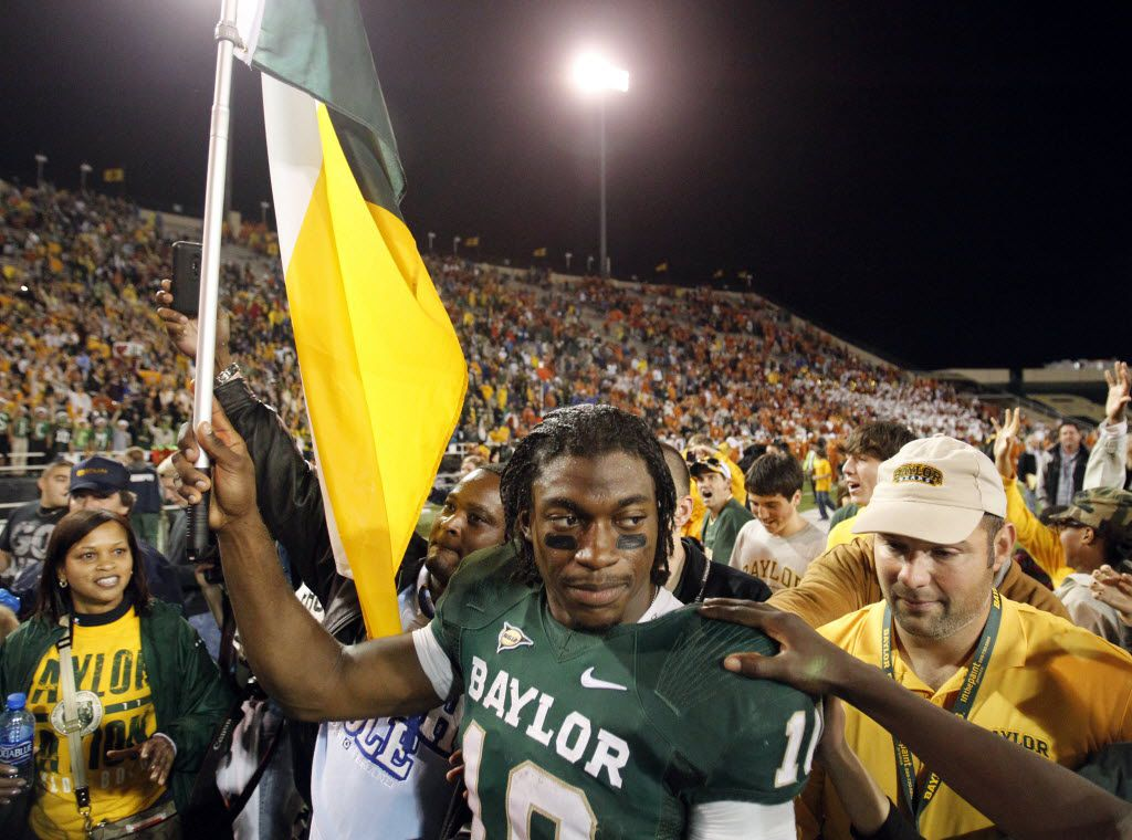 Baylor Bears quarterback Robert Griffin III (10) carries a flag as fans and teammates gather around him after the game between the University of Texas and Baylor University at Floyd Casey Stadium in Waco on December 3, 2011. Baylor defeated Texas 48-24. (Vernon Bryant/The Dallas Morning News)