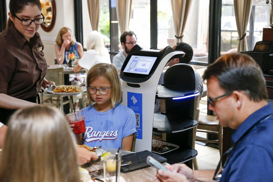 A server removes food from the food delivery robot Panchita at La Duni in Dallas. The young customers hardly even notice.