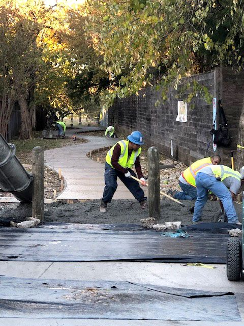 Workers pour the new sidewalk on Nov. 18, 2019, as work continued to revitalize an abandoned alley in the Cochran Heights neighborhood of Dallas.
