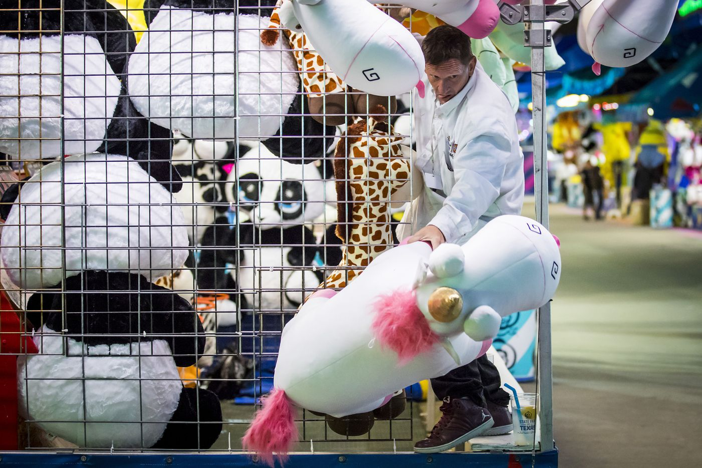 Michael Jenkins, 53, restocks prizes on the Midway after closing time at the State Fair of Texas.
