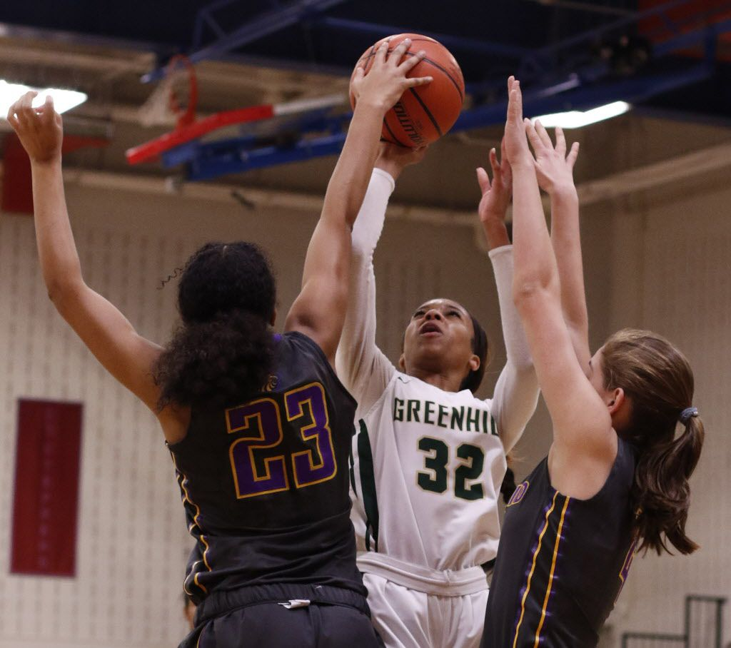Greenhill's Kionce Woods (32) shoots a jump shot over the defense of Houston Kincaid defenders December Stevenson (23) and Olivia Sullivan (4) during second half action.  The two teams played in the girls basketball title game of the SPC Championships held at Country Day School in Fort Worth on February 16, 2019.