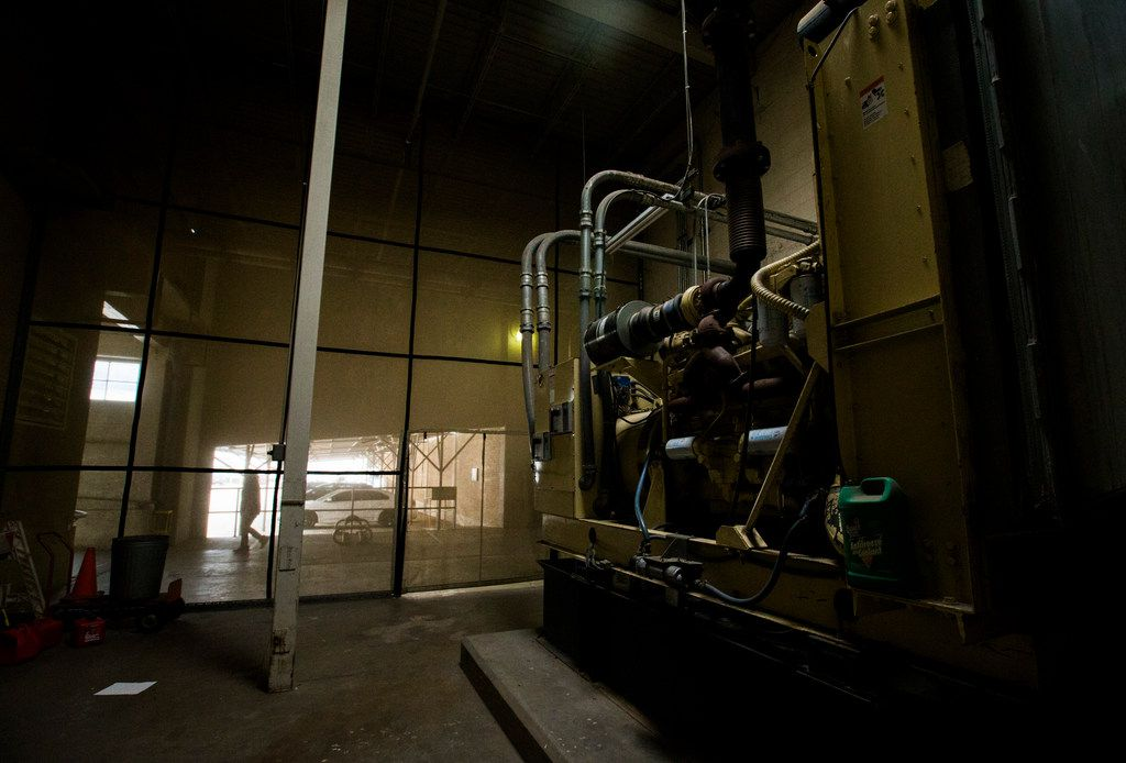 An employee passes large machinery kept hidden by a wall of mesh near the back entrance of 508 Young Street.