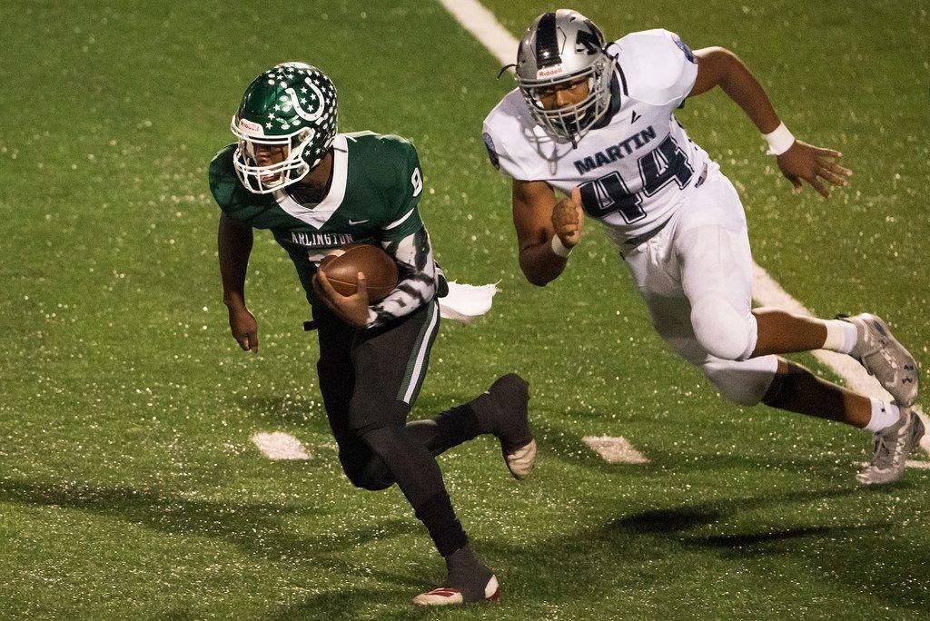 Arlington Martin defensive lineman Ernest Cooper IV chases down Arlington quarterback Kris Sims (8) during the second half of a high school football game at UTA's Maverick Stadium on Friday, Oct. 18, 2019, in Arlington, Texas.