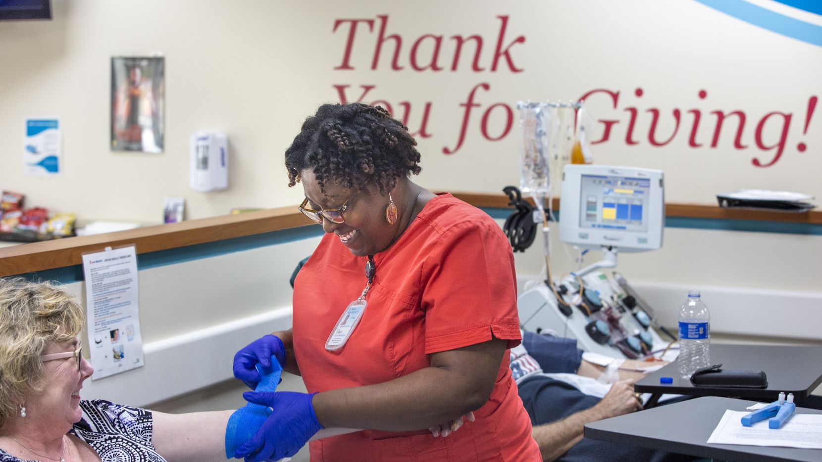 Donor Center supervisor Nicole Taylor (center) laughs with longtime blood donor Diana Tipton as she prepares to draw blood at the Carter BloodCare Preston Valley Donor Center in Dallas on Wednesday, March 18, 2020.