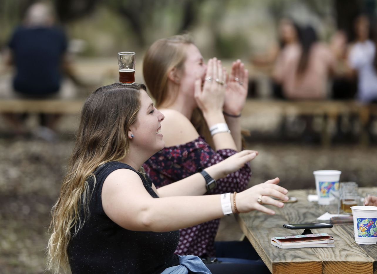 Baileigh Millender of Rockwall balances a glass on her head as Caroline Kimbell of Austin laughs at Family Business Beer Company in Dripping Springs.