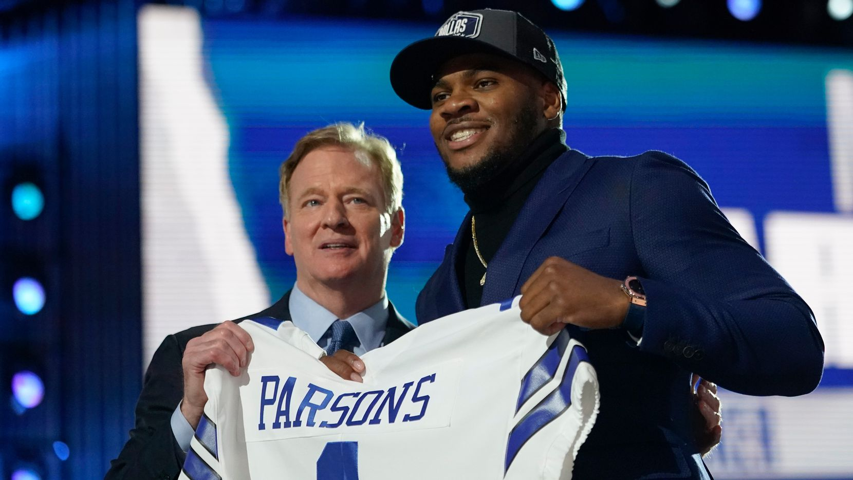 Penn State linebacker Micah Parsons, right, holds a team jersey with NFL Commissioner Roger Goodell after the was chosen by the Dallas Cowboys with the 12th pick in the NFL football draft Thursday, April 29, 2021, in Cleveland.