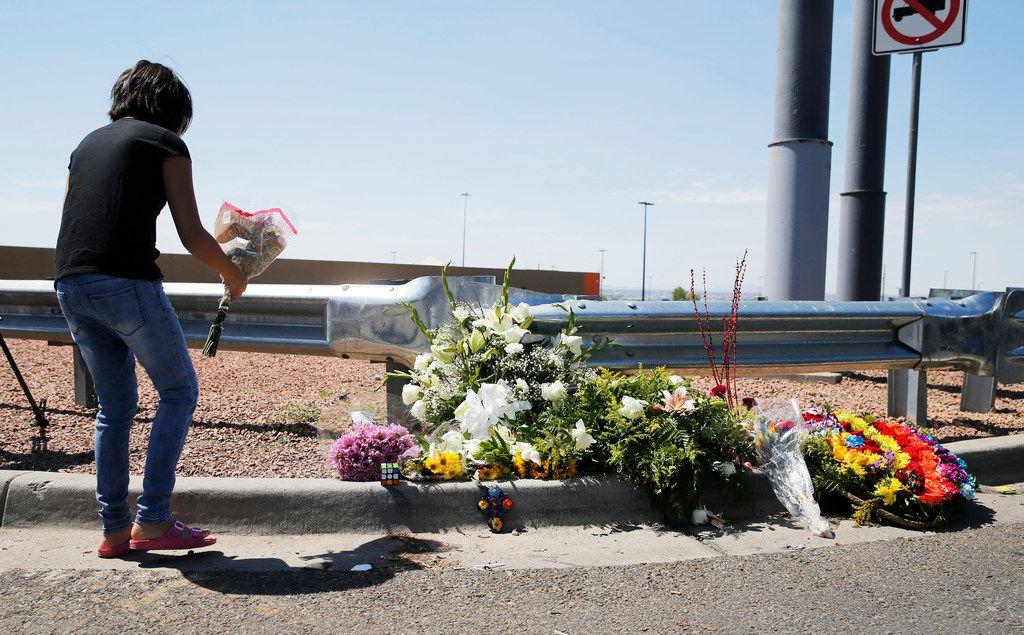 Leilani Hebben, 11, of El Paso leaves flowers near an entrance to the Walmart.