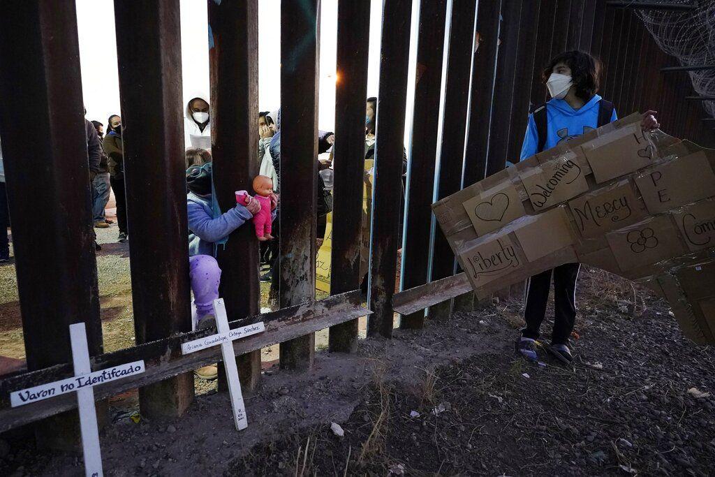 Una niña en México mete su muñeca entre las barreras de la valla fronteriza de Estados Unidos mientras mira a Nathan Adams Maldonado, a la derecha, el martes 15 de diciembre de 2020 durante un evento con varias familias que buscan asilo, en Douglas, Arizona.