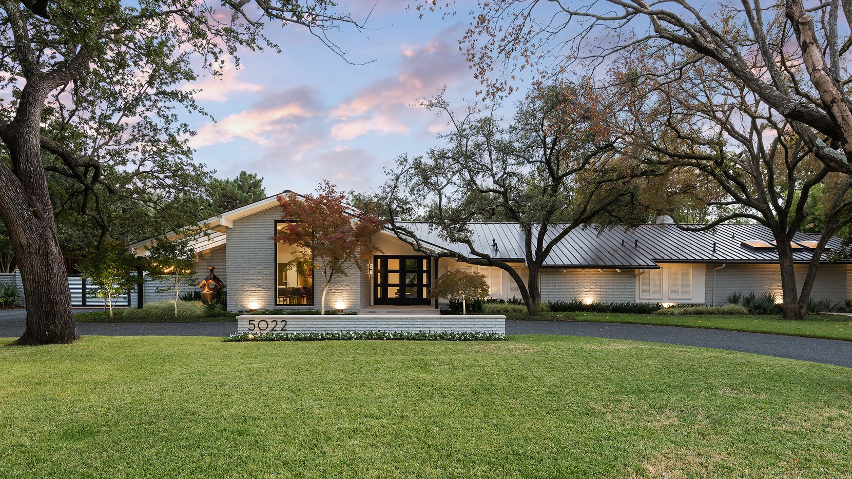 The entrance to 5022 Pebblebrook Drive in North Dallas leads into a large and open living space with French doors and windows overlooking the patio.