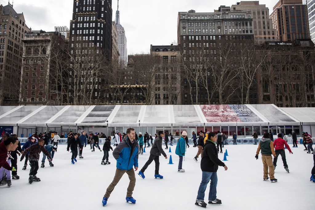 People skate on a temporary ice rink set up in Bryant Park as part of a winter carnival in New York City.