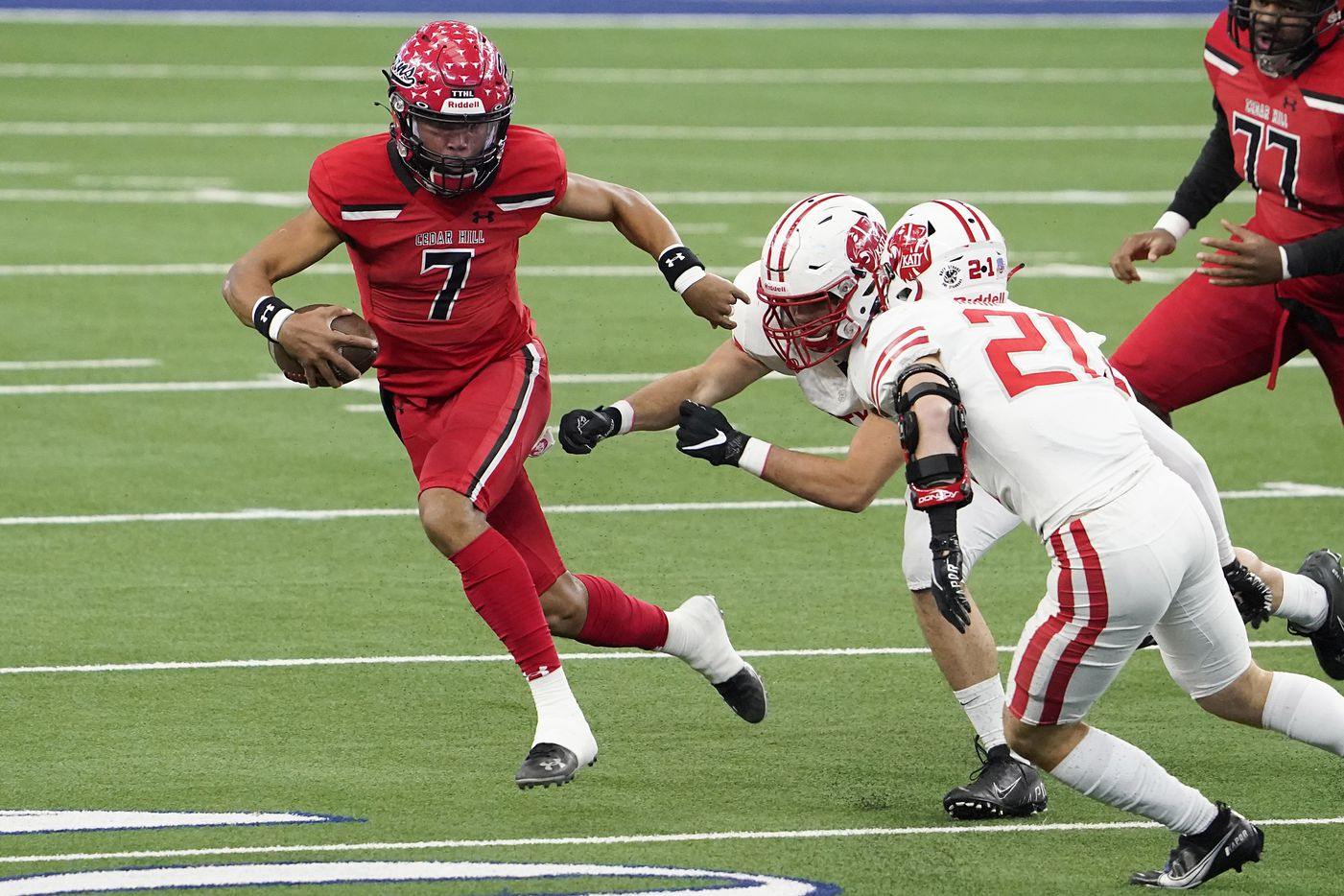 Cedar Hill quarterback Kaidon Salter (7) is chased down by Katy defensive lineman Cayde Robertson and Carson Marshall (21) during the first half of the Class 6A Division II state football championship  game at AT&T Stadium on Saturday, Jan. 16, 2021, in Arlington, Texas.