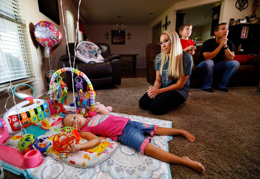 The Magallons of Burleson are one of many families who say they've considered divorce so that their sick or disabled children can be cared for through the unemployed parent's Medicaid. The situation is informally advised to many Texas families. Jayme Magallon watches as her 3-year-old daughter Annalynne plays among her birthday balloons as her husband Brandon Magallon (right) and 4-year-old son Acetyn watch television at their Burleson home on Friday, July 13. Annalynne suffers from cerebral palsy.