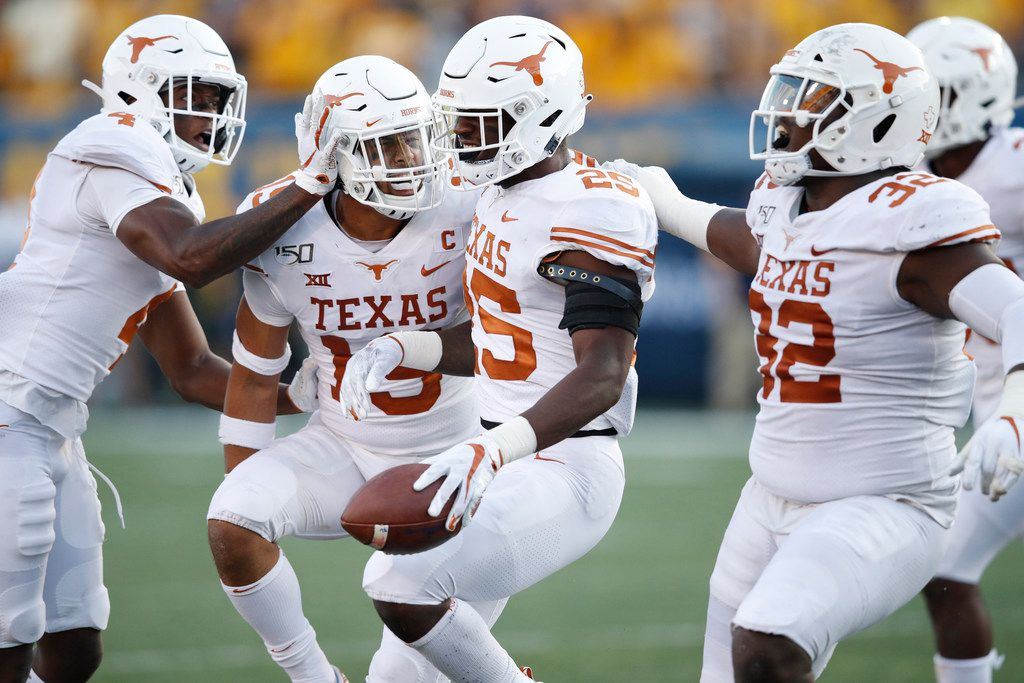 MORGANTOWN, WV - OCTOBER 05: B.J. Foster #25 of the Texas Longhorns celebrates with teammates after intercepting a pass in the second half against the West Virginia Mountaineers at Mountaineer Field on October 5, 2019 in Morgantown, West Virginia.